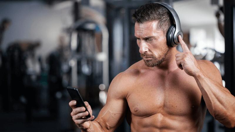 Sportlicher Mann mit Kopfhörern und Handy